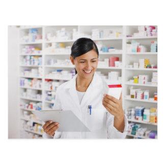 Farmacéutico en la farmacia que sostiene el tabler postales