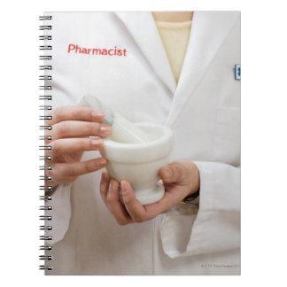 Farmacéutico que sostiene el mortero y la maja spiral notebook
