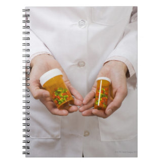 Farmacéutico que sostiene las botellas de píldora libro de apuntes con espiral