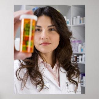 Farmacéutico que sostiene una botella de píldora póster