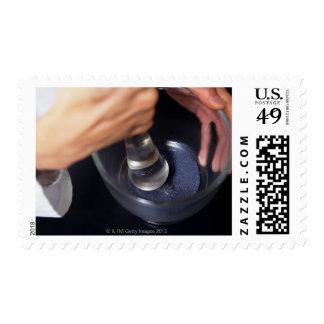 Farmacéutico que usa el mortero y la maja en la timbre postal