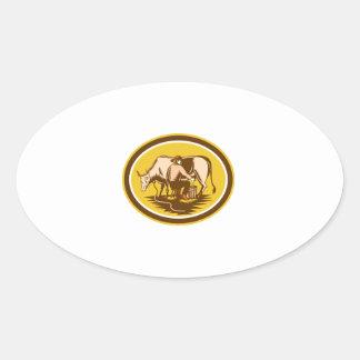 Farmer Milking Cow Oval Woodcut Oval Sticker