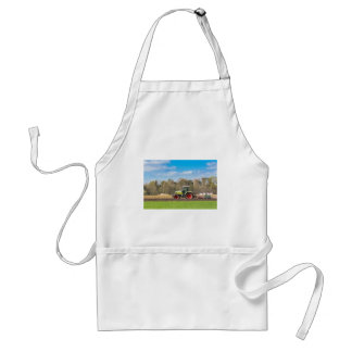Farmer on tractor plowing sandy soil in spring adult apron
