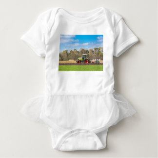 Farmer on tractor plowing sandy soil in spring baby bodysuit