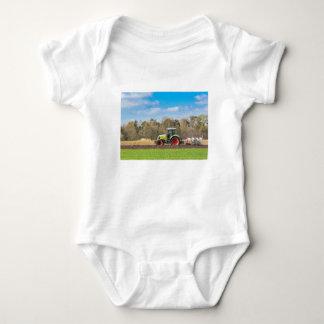Farmer on tractor plowing sandy soil in spring baby bodysuit