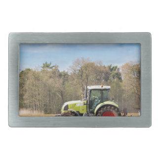 Farmer on tractor plowing sandy soil in spring belt buckle