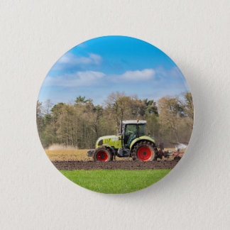 Farmer on tractor plowing sandy soil in spring button