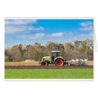 Farmer on tractor plowing sandy soil in spring card