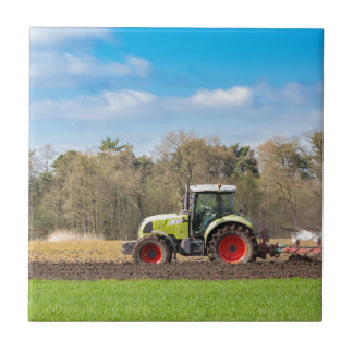 Farmer on tractor plowing sandy soil in spring ceramic tile