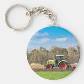 Farmer on tractor plowing sandy soil in spring keychain
