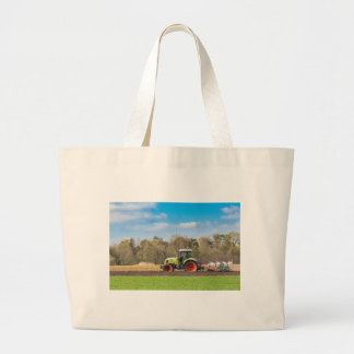 Farmer on tractor plowing sandy soil in spring large tote bag