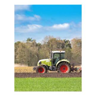 Farmer on tractor plowing sandy soil in spring letterhead