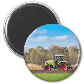 Farmer on tractor plowing sandy soil in spring magnet