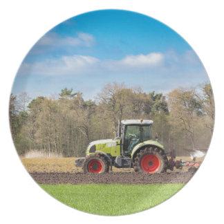 Farmer on tractor plowing sandy soil in spring melamine plate