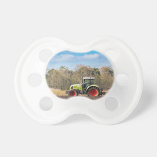 Farmer on tractor plowing sandy soil in spring pacifier