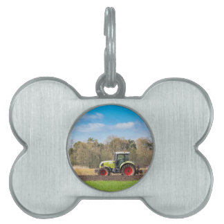 Farmer on tractor plowing sandy soil in spring pet tag