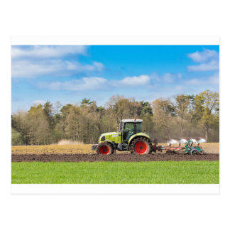 Farmer on tractor plowing sandy soil in spring postcard