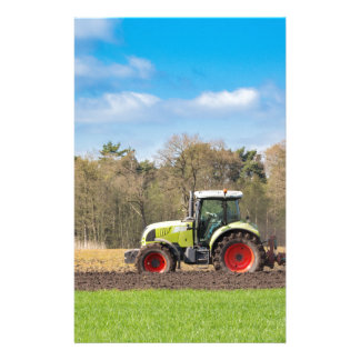 Farmer on tractor plowing sandy soil in spring stationery