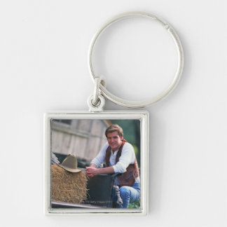Farmer posing by pickup truck with hay bale keychain