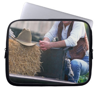 Farmer posing by pickup truck with hay bale laptop sleeve