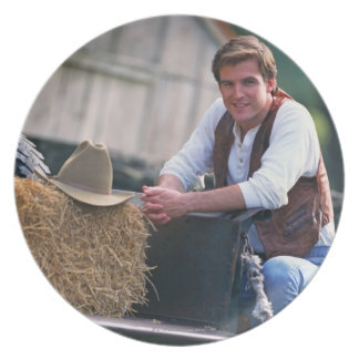 Farmer posing by pickup truck with hay bale dinner plate