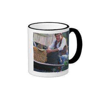 Farmer posing by pickup truck with hay bale ringer mug