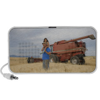 Farmer with a 5 year old girl in a field of 2 mini speakers