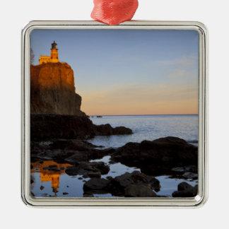 Faro partido de la roca en la puesta del sol cerca adorno navideño cuadrado de metal