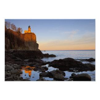Faro partido de la roca en la puesta del sol cerca cojinete