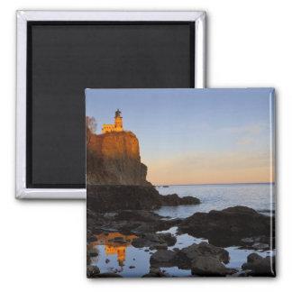 Faro partido de la roca en la puesta del sol cerca imán cuadrado