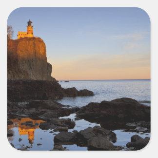 Faro partido de la roca en la puesta del sol cerca pegatina cuadrada