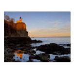 Faro partido de la roca en la puesta del sol cerca postales