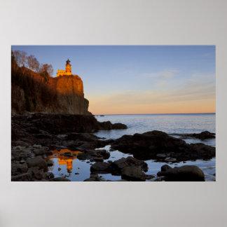 Faro partido de la roca en la puesta del sol cerca póster