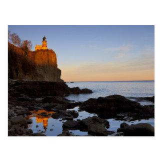 Faro partido de la roca en la puesta del sol cerca tarjetas postales