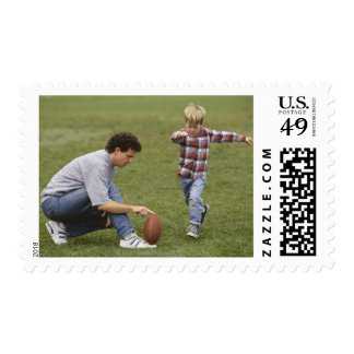 Father and son (4-6) playing American football Postage