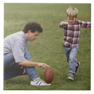 Father and son (4-6) playing American football Ceramic Tiles