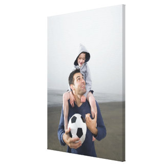 Father carrying son on shoulders and holding canvas print