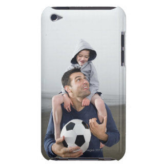 Father carrying son on shoulders and holding iPod touch case
