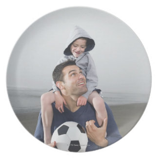 Father carrying son on shoulders and holding melamine plate