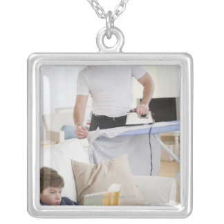 Father ironing silver plated necklace