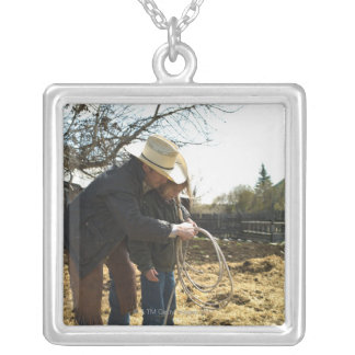 Father teaching daughter how to use lasso on square pendant necklace