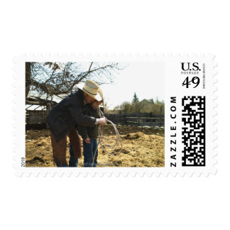 Father teaching daughter how to use lasso on postage
