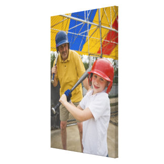 Father with daughter at batting cage canvas print