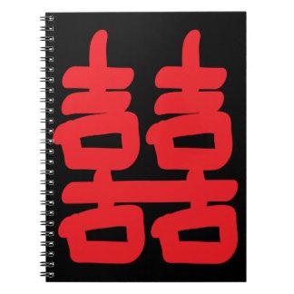 Felicidad doble en cuaderno rojo