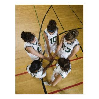 Female basketball team having group handshake, postcards