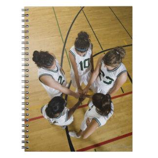 Female basketball team having group handshake, spiral notebook