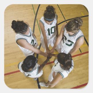 Female basketball team having group handshake, square sticker