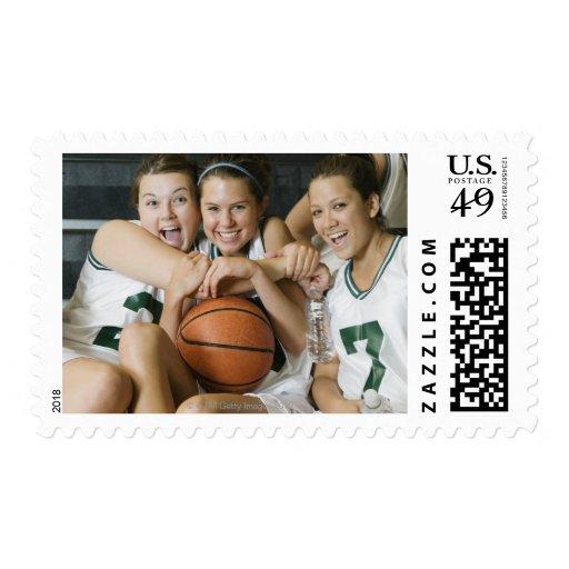 Female basketball team smiling, portrait stamps