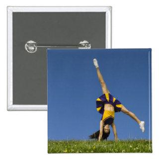 Female cheerleader doing cartwheel 2 inch square button