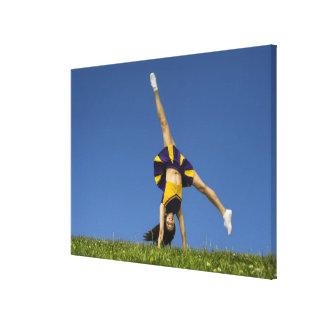 Female cheerleader doing cartwheel canvas print